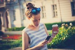 学生女孩在有智能手机和咖啡的城市 免版税库存图片