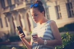 学生女孩在有智能手机和咖啡的城市 免版税库存照片