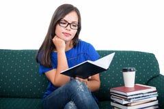 学生女孩坐从笔记本的长沙发读书 免版税库存照片