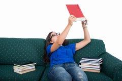 学生女孩坐学习从笔记本的长沙发 免版税库存照片