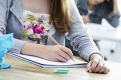 学生女孩文字测试在教室 免版税图库摄影