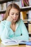 学生女孩阅读书在图书馆里 免版税图库摄影