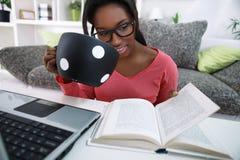 学生女孩饮用的咖啡和学会 免版税库存图片