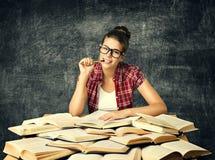 学生学习参考书,年轻大学妇女读了许多书ov 免版税图库摄影