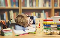 学生孩子睡觉在学校的,疲乏的孩子睡着在桌上 免版税库存图片