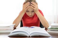 学生对他的家庭作业是沮丧和疲乏 图库摄影