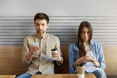 学生年轻夫妇坐在快餐,饮用的咖啡的一个日期,看在手机,忽略 库存照片