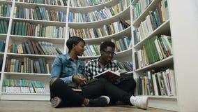 学生年轻非洲夫妇坐地板在书架附近,当准备对检查在图书馆里时 股票视频