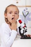年轻学生惊奇什么她在显微镜看见了 免版税图库摄影