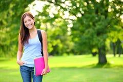 学生拿着书和背包的女孩画象 免版税库存照片