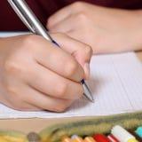 学生文字用在他的练习本的手在学校 免版税库存照片