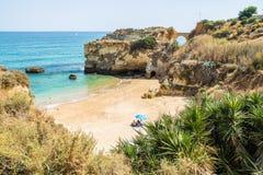 学生海滩或普腊亚dos Estudantes在拉各斯,葡萄牙 在海滩的一夫妇选址在一把蓝色遮阳伞下 免版税库存照片