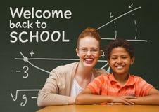 学生男孩和老师在桌上反对绿色黑板有欢迎的到学校课文 库存例证