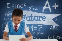 学生男孩在使用一种片剂的桌上反对有未来文本的蓝色黑板 库存图片