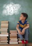 学生男孩坐查寻反对有学校和教育图表的绿色黑板的桌 免版税库存照片