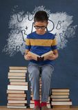 学生男孩坐桌读书反对有学校和教育图表的蓝色黑板 免版税图库摄影