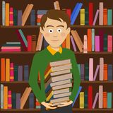 学生男孩站立反对书架的举行堆书在图书馆里 免版税库存图片