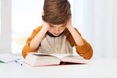学生男孩阅读书或课本在家 库存图片