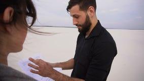 学生男性同意女商人买的地皮在咖啡馆的海边 股票视频
