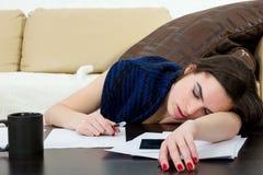 学生疲倦了和睡觉在她的在笔记的客厅 库存照片