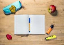 学生的工作区有被打开的习字簿的,案件,笔,苹果,秋天枫叶,在书桌上的标志 图库摄影