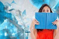 学生的画象的综合图象掩藏在一本蓝皮书后的 免版税图库摄影