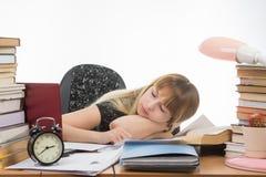 学生睡着了在准备好的桌上通过毕业项目 免版税库存图片