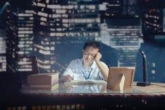 学生睡着,当学习在书桌时 在玻璃后被射击的办公室室 免版税库存照片