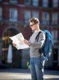 年轻学生背包徒步旅行者旅游看的城市地图在假日移动 免版税库存照片