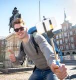 学生背包徒步旅行者旅游采取的selfie照片用棍子和手机户外 免版税库存照片