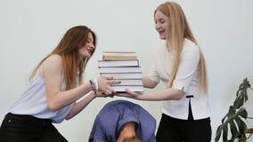 学生获得乐趣并且使用与书 高中学生在他们的朋友` s头上把书放 影视素材