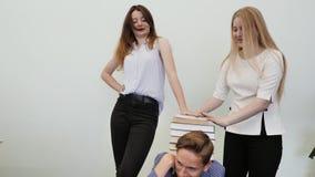 学生获得乐趣并且使用与书 高中学生在他们的朋友` s头上把书放 股票视频