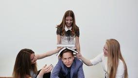 学生获得乐趣并且使用与书 高中学生在他们的朋友` s头上把书放 股票录像