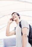 学生谈话在电话在机场 免版税库存照片