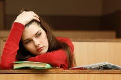 学生青少年的女孩在空的教室大学疲倦了 库存图片