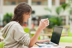学生饮用的咖啡,当使用膝上型计算机在自助食堂桌时 库存照片