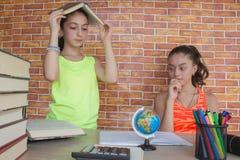 学生,两工作在他的家庭作业的女孩 写俏丽的女孩高中的学生画象学习和 库存图片
