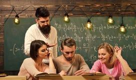 学生,小组联接讲话,请求忠告,老师解释学习困难概念 有胡子的老师 免版税库存照片