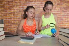 学生,工作在他的家庭作业的两个女孩 有许多的两个女孩书学习为检查的 免版税库存图片