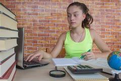 学生,工作在他的家庭作业的女孩 在家坐在书桌的女孩,做家庭作业 库存照片
