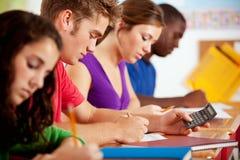 学生:聪明男性青少年使用家庭作业的计算器 免版税库存图片