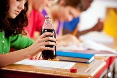 学生:青少年的学生有喝的瓶苏打在类期间 免版税图库摄影