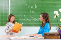 学生读了一位妇女老师在黑板 库存图片