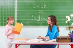 学生读了一位妇女老师在黑板 免版税图库摄影