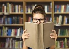 学生读的开放书、眼睛在玻璃和书封口盖板 免版税库存照片