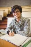 年轻学生画象坐书桌读书笔记 免版税图库摄影
