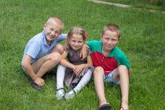 学童坐草,愉快的孩子坐草、女孩和两个男孩 免版税库存图片