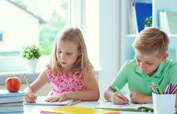 学童是回来了到学校和学会在桌上在教室 免版税库存照片