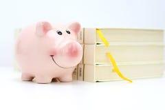 学院与站立在堆的存钱罐的资金概念书附近 免版税库存图片