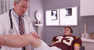 学院炫耀有中间年迈的医生审查的膝盖injur的运动员 免版税库存图片